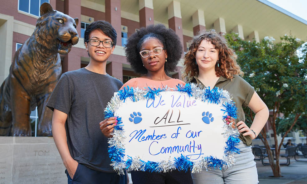 "three UofM students holding poster that says ""We value all members of our community"""