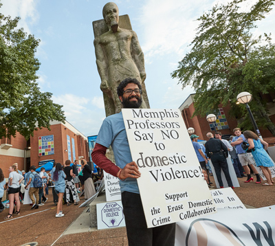 """faculty member at """"Walk a Mile in Her Shoes"""" event holding sign that says """"Memphis Professors say NO to domestic violence. Suppport the Erase Domestic Crime Collaborative"""""""