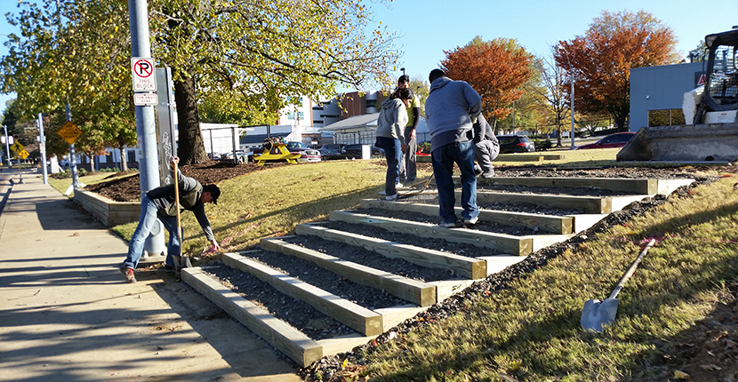 Students and volunteers make final touches on steps constructed at the Edge Triangle Park design-build.