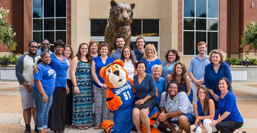 UofM mascot Pouncer and umParents staff in front of University Center bronze statue.