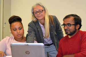 faculty instructing with laptop to two students