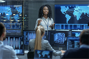 female speaking with computer monitors and screens in background