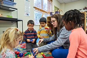 preschool teacher playing with preschool children