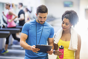 personal trainer showing clipboard to female with towel around her neck