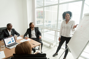 female professional presenting to group of colleagues
