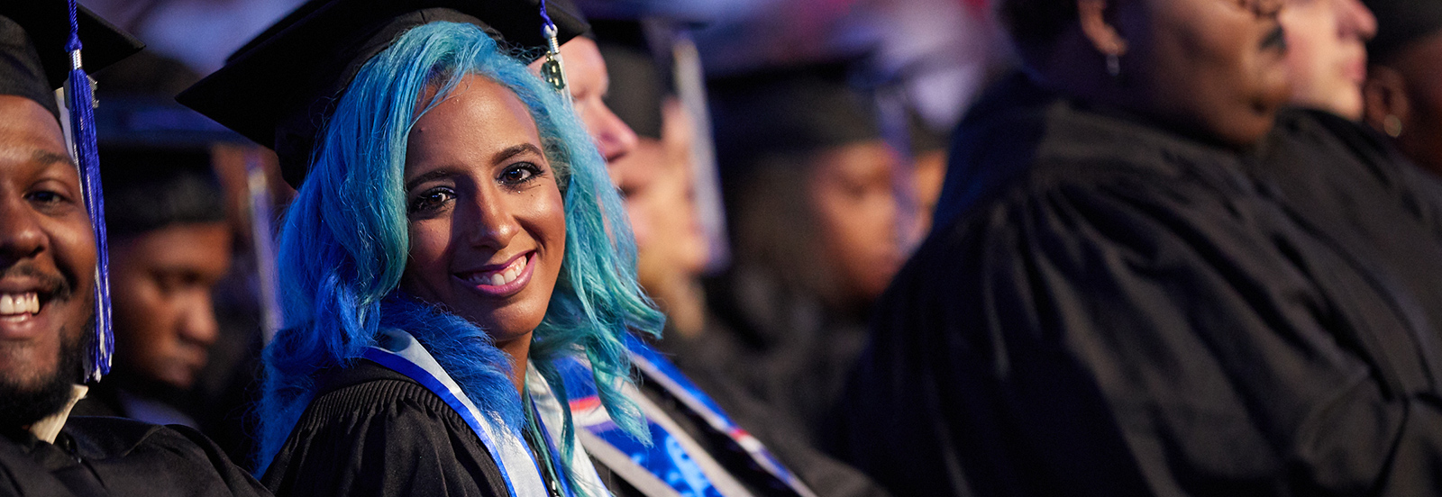 LiFE graduate with blue hair sitting in audience of graduates in commencement regalia