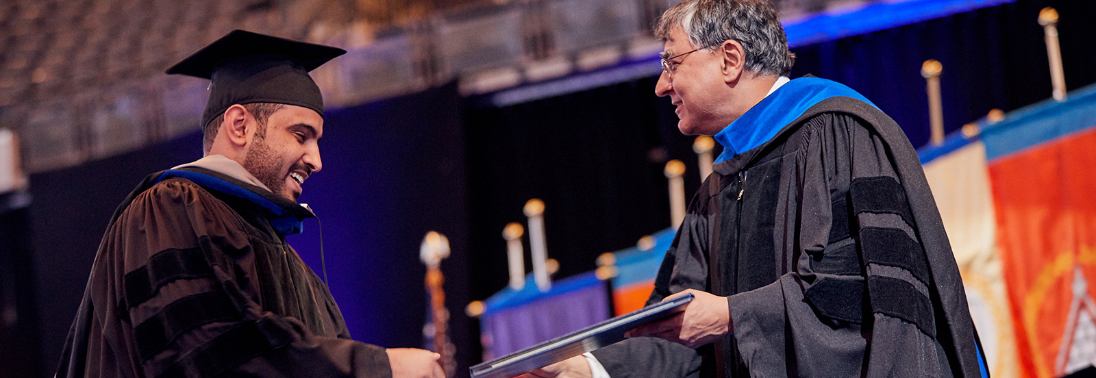 male student shakes hand of dean while receiving diploma at Commencement