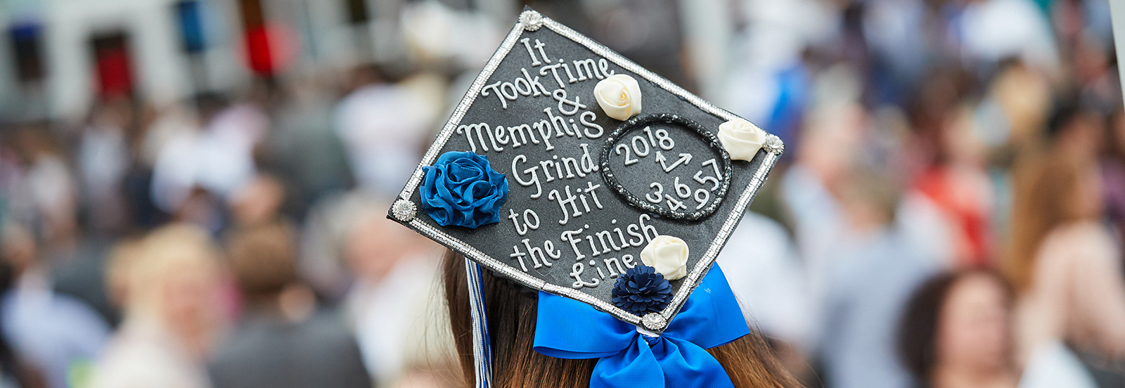 Student at commencement with mortar board that reads: It took time and Memphis grind to get to the Finish Line