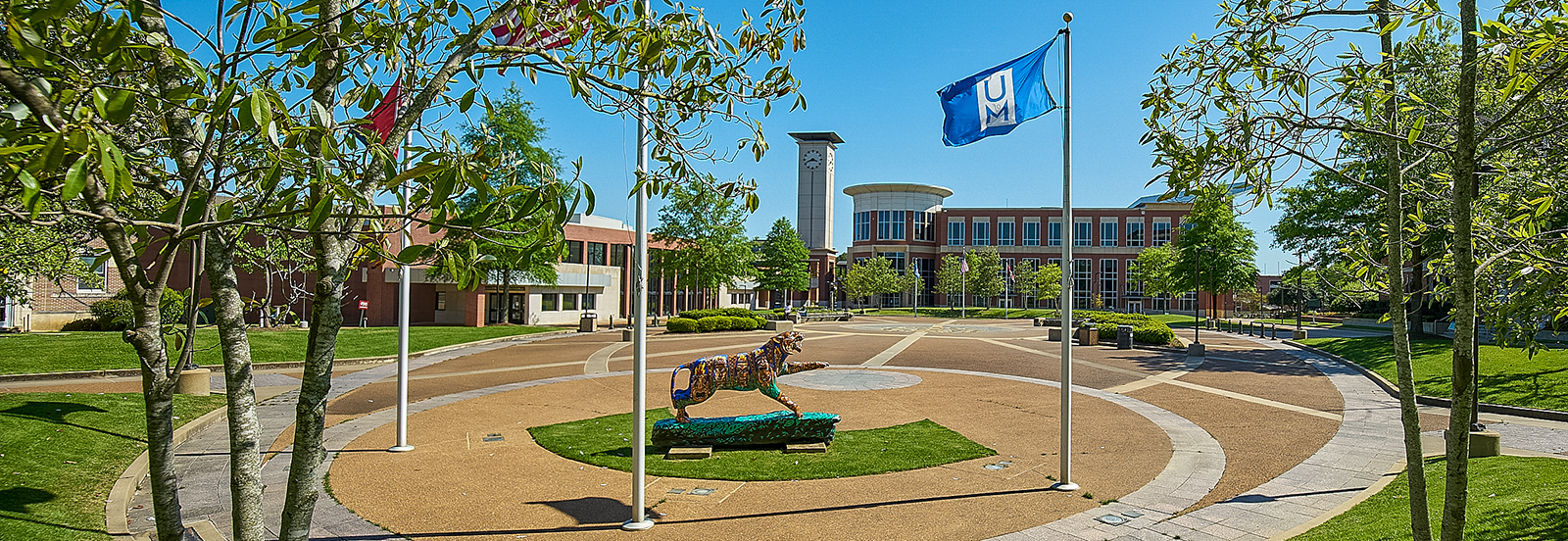 UofM Student Plaza with tiger statue, UofM flags and University Center in the background