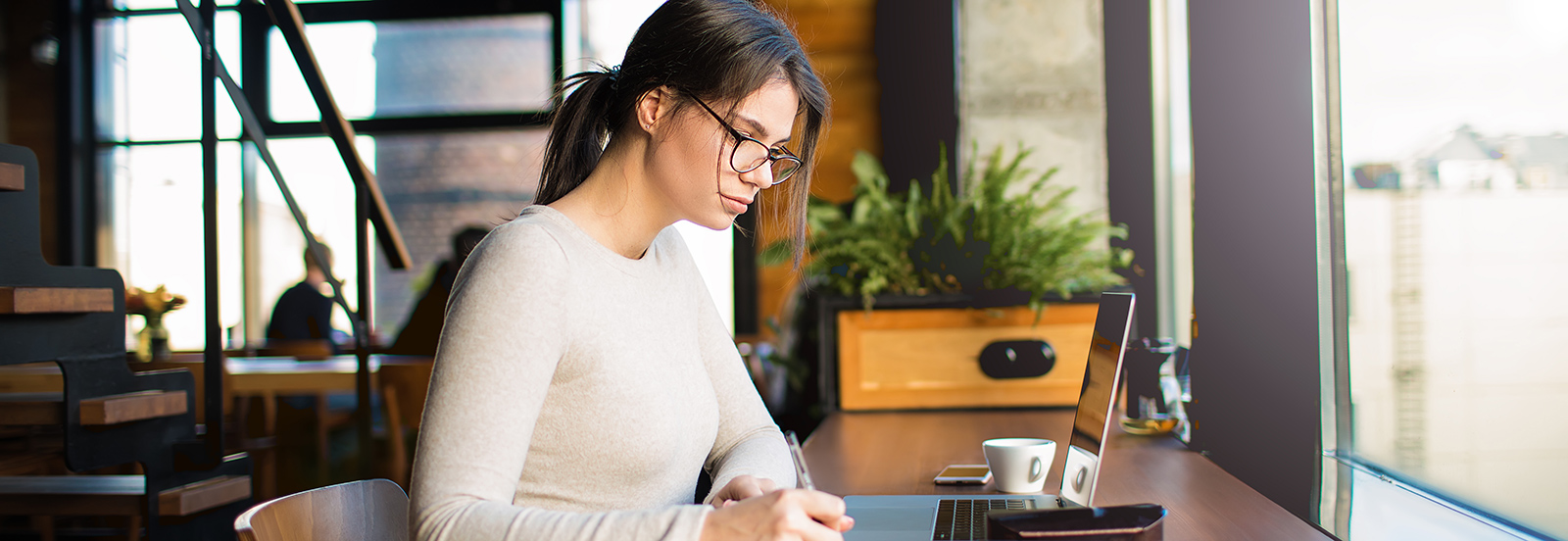 female working on laptop in coffee shop