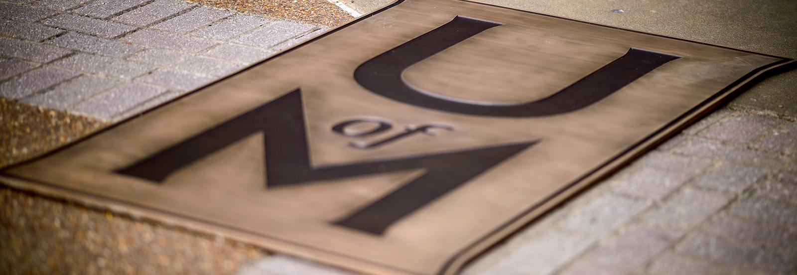 bronze UofM logo in sidewalk